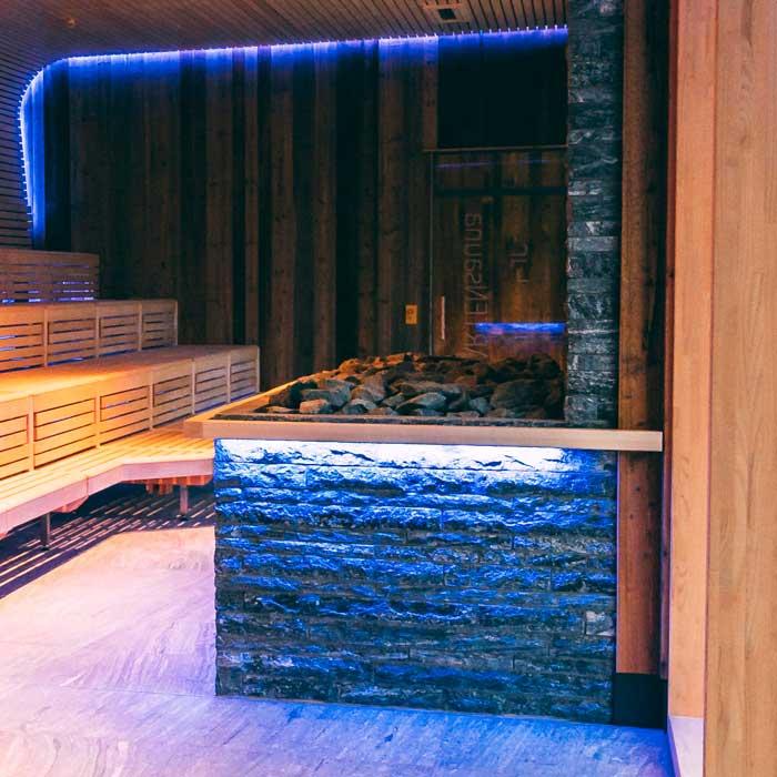In Naturstein-Optik verkleideter Saunaofen-Bereich