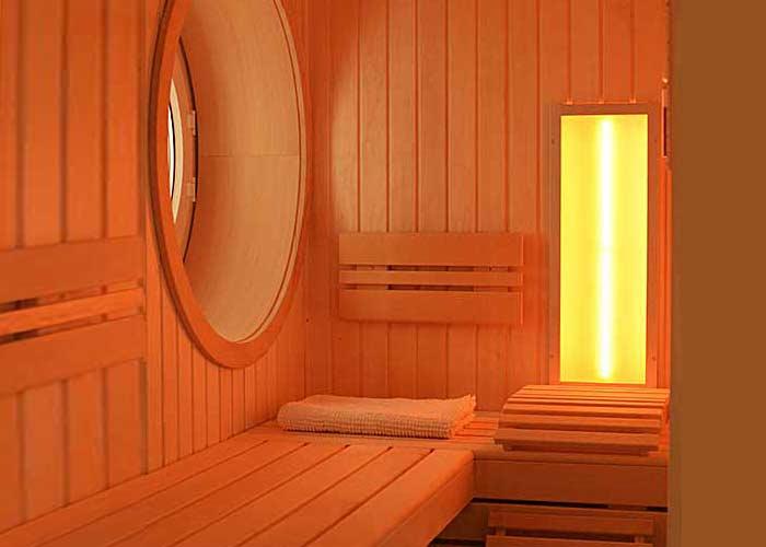 Handwerklich anspruchsvoll: Innensauna aus Espenholz mit kreisrundem Fenster